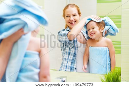 Happy Family In Bathroom. Mother Of A Child With Towel Dry Hair