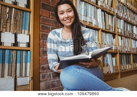 Smiling student sitting on the floor against wall in library reading book at the university