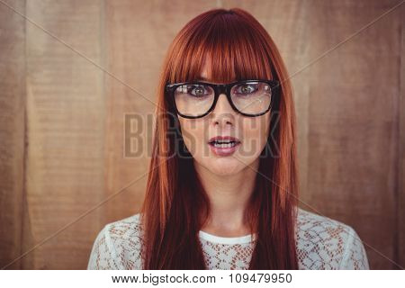 Surprised hipster woman posing face to the camera against wooden background