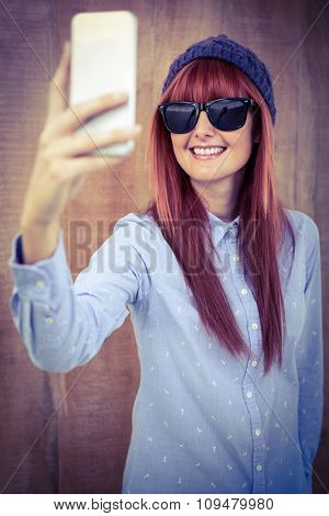 Smiling hipster woman taking selfie against wooden background