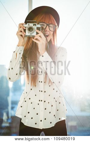 Smiling hipster woman taking pictures in a bright room