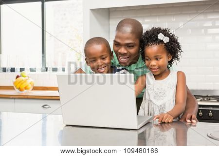 Father using laptop with his children in kitchen in kitchen at home