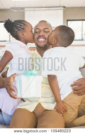 Happy father is kissed by his two children in living room
