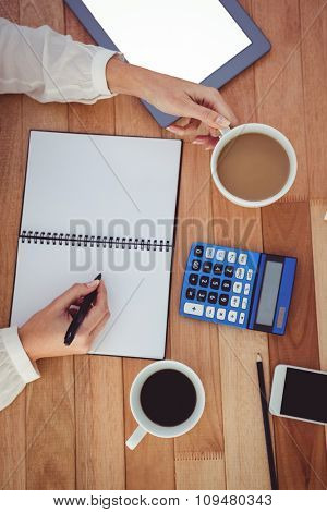 Cropped image of woman with coffee cup writing on notepad in her office