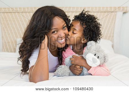 Young girl kissing her smiling mother on bed at home