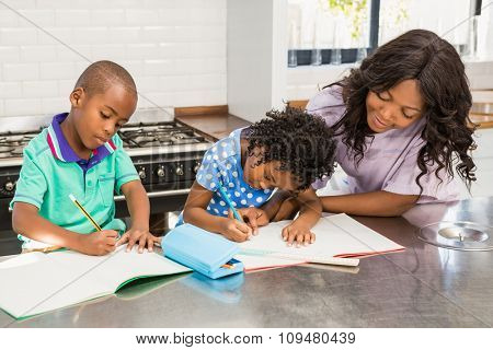 Children doing homework with their mother in the kitchen