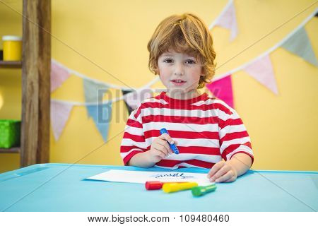 Playful kid colouring in a picture at the desk
