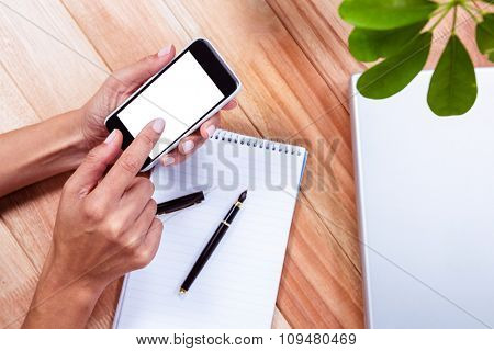 Overhead of feminine hands using smartphone with notebook on table