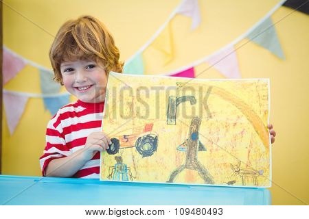 Smiling child holding up his finished painting at the desk