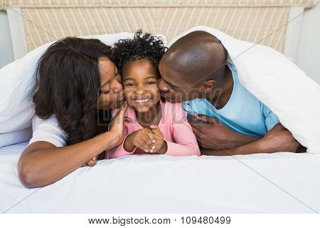 Parents kissing their daughter on bed