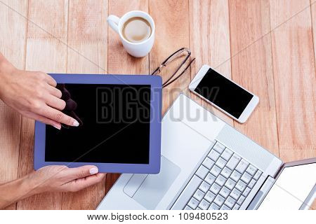 Overhead of feminine hands using tablet with laptop and coffee on desk