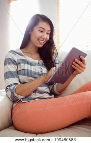 Smiling asian woman using tablet on couch at home in the living room