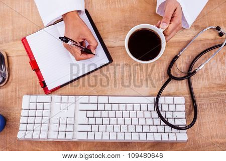 Doctor holding coffee cup and writing on diary on desk
