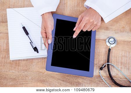 Doctor using digital tablet on desk