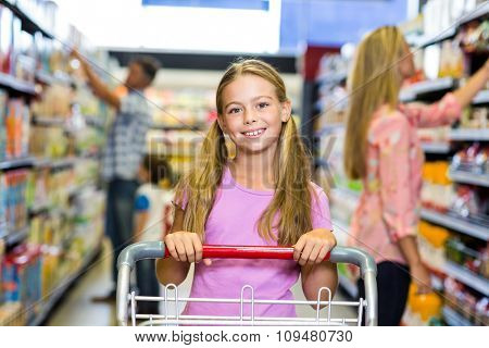 Smiling child with her family in the supermarket