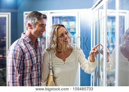 Smiling couple pointing food in supermarket fridge