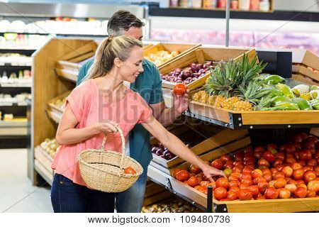 Happy couple at the supermarket holding tomatoes