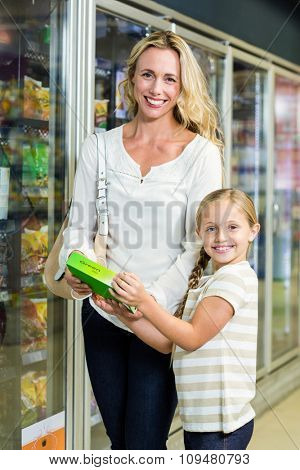 Mother and daughter at the supermarket smiling at the camera