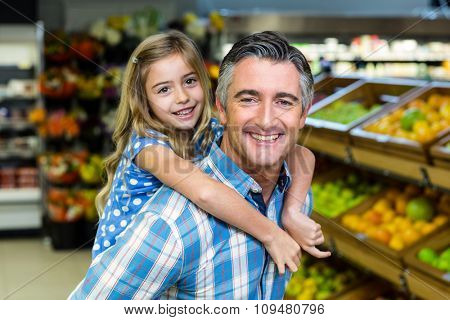 Daughter staying on her fathers back in supermarket