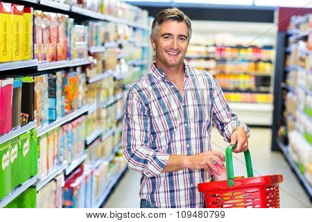 Man smiling at the camera while buying food in supermarket