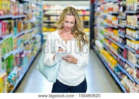 Blonde woman checking list at supermarket