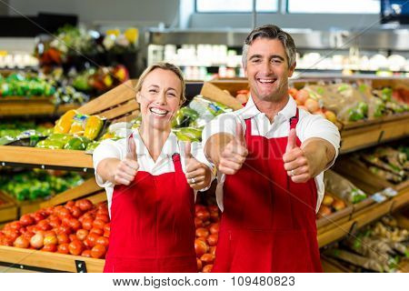 Smiling couple showing thumbs and wearing apron in supermarket