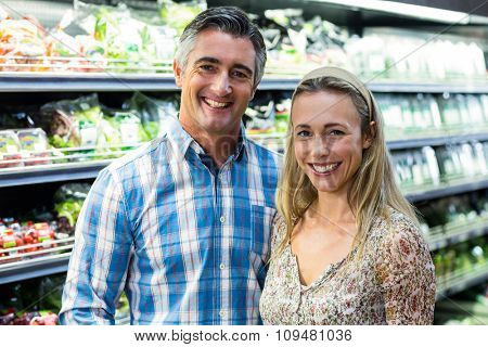 Happy smiling couple posing together at supermarket