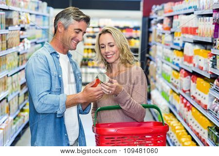 Smiling couple holding canned food at supermarket