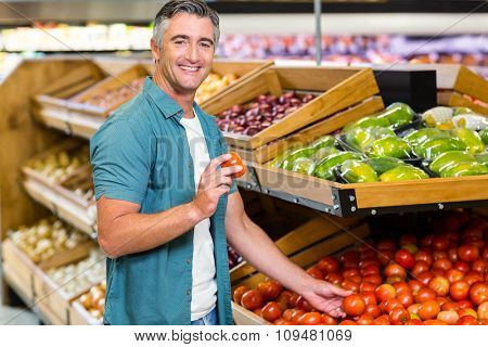 Smiling man choosing a tomato at supermarket
