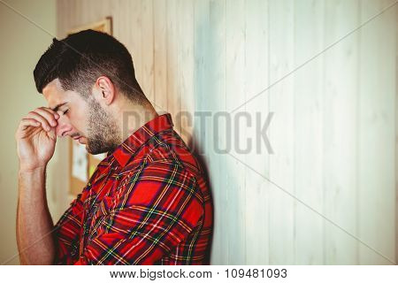 Handsome hipster feeling stressed out on wooden background
