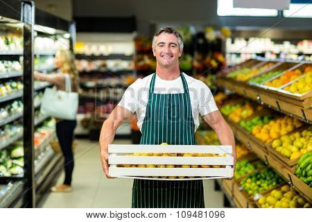 Smiling worker carrying vegetables box in supermarket