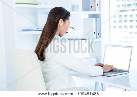Businesswoman in white shirt using laptop at the desk in work
