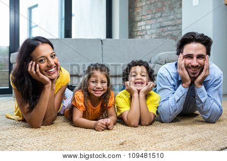 Smiling family on carpet in living room posing for the camera