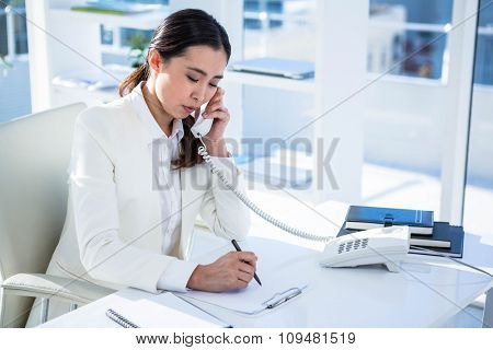 Focused businesswoman on her telephone at the desk in work