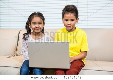 Young smiling siblings using laptop in living room