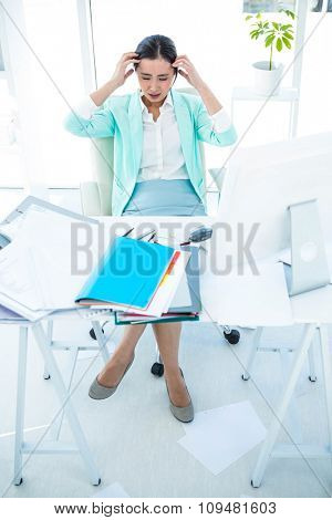 Stressed out business woman at the desk in work