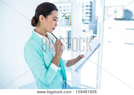 Businesswoman using her notes at the desk in work
