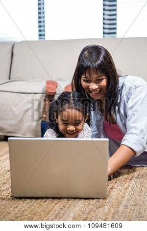 Happy young mother using laptop with her daughter in living room