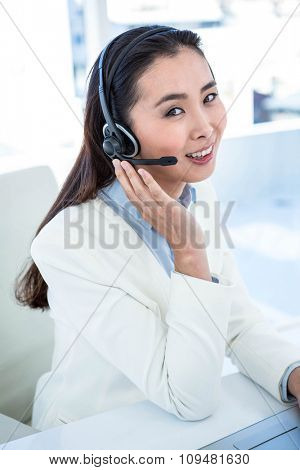 Smiling businesswoman with headset at the desk in work