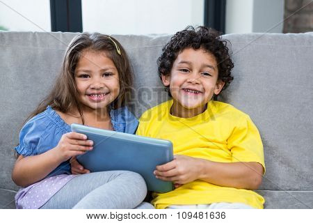 Smiling siblings using tablet on the sofa in living room
