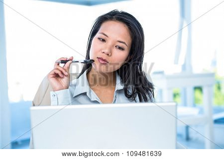 Smiling businesswoman with pen using laptop at the desk in work