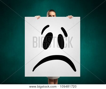 Portrait of a young attractive woman with sad smiley on banner