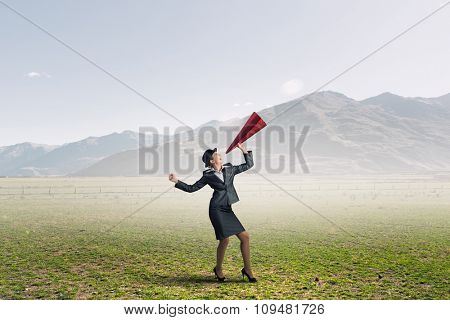 Young woman in suit and bowler hat screaming in paper trumpet
