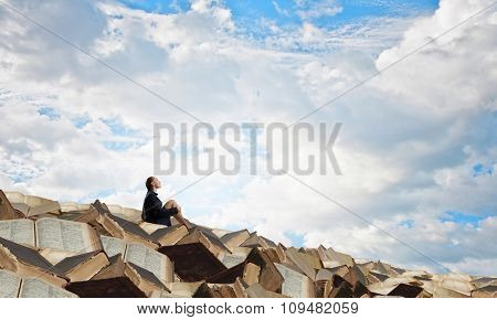 Bored young businesswoman sitting alone on pile of books