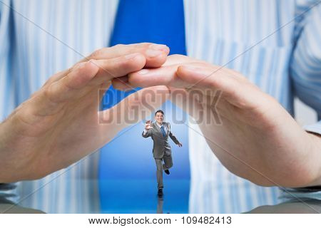 Miniature of running businessman protected with hands