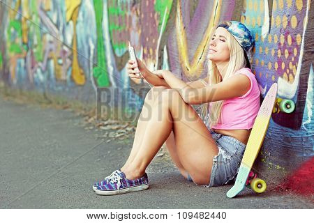 Young woman with skating board and smartphone sitting on asphalt on painted wall background