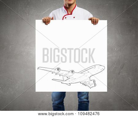 Unrecognizable man showing white banner with airplane design
