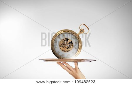 Waiter holding silver platter with old pocket watch