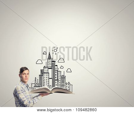 Young man in casual holding opened book with construction concept