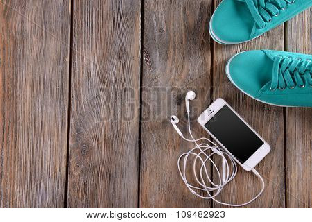 White cellphone with headphones and gumshoes on varnished wooden background